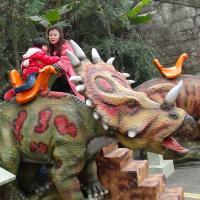 Man-made synthetic dinosaur mounts walking dinosaur